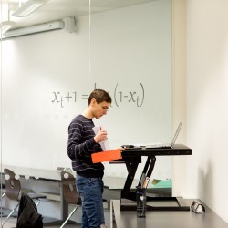 Person reading laptopscreen at a standing desk