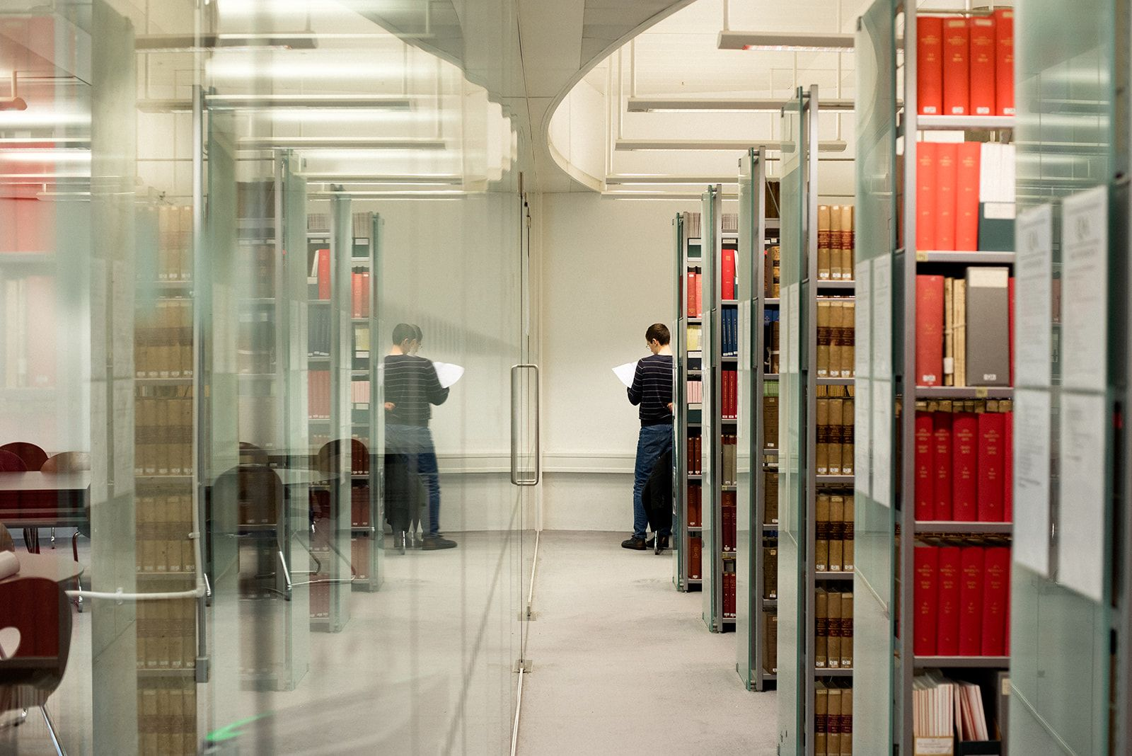 Corridor of shelves at the Moore Library with person consulting journal