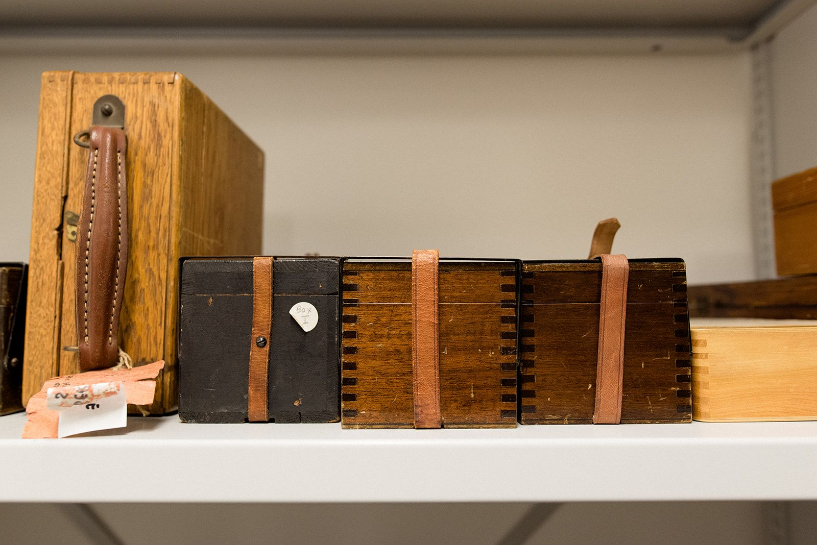 Image shows a variety of wooden storage boxes on a shelf.