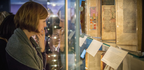 Image of a Friend looking at manuscripts in an exhibition case.